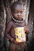 Himba girl with can looking at the camera