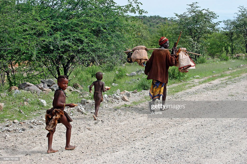 Himba tribe children and man carrying merchandise along dirt road Kaokoland / Kaokoveld Kunene Region Namibia South Africa