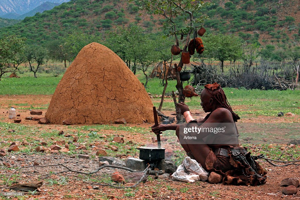 Himba woman cooking in front of traditional mud hut Kaokoland / Kaokoveld Kunene Region Northern Namibia South Africa