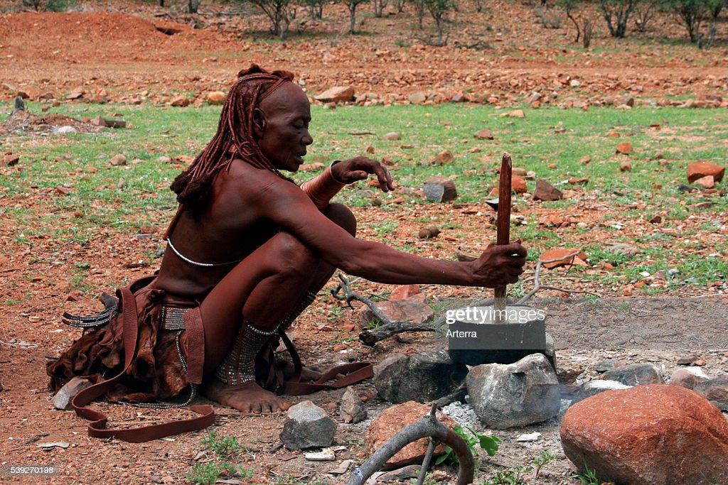 Himba woman cooking in pot on open fire Kaokoland / Kaokoveld Kunene Region Northern Namibia South Africa