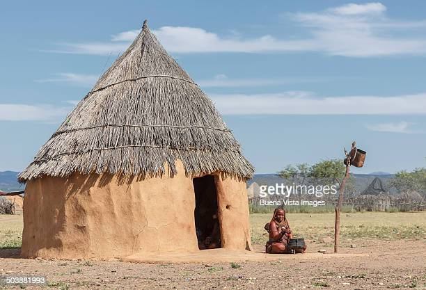 Himba woman cooking near her hut