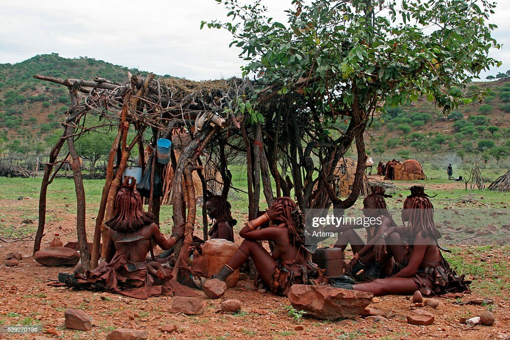 Himba women in traditional village with mud huts Kaokoland / Kaokoveld Kunene Region Northern Namibia South Africa
