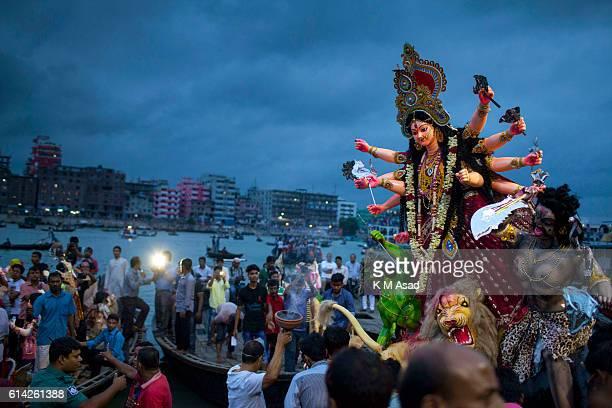 DHAKA SHADARGHAT DHAKA BANGLADESH Hindu community devotees immerse an idol of Hindu Goddess Durga into the river Buriganga The Hindu community people...