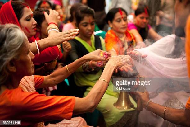 Hindu community women gather to take holy smoke from their ritual for Hindu god Bipadtarini Devi in Dhaka Bangladesh July 25 2015 During the ritual...