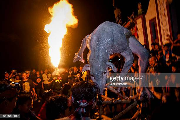 Hindu devotee breath a fire as they carry a effigy known as 'OgohOgoh' during a parade on March 30 2014 in Yogyakarta Indonesia Balinese Hindus hold...