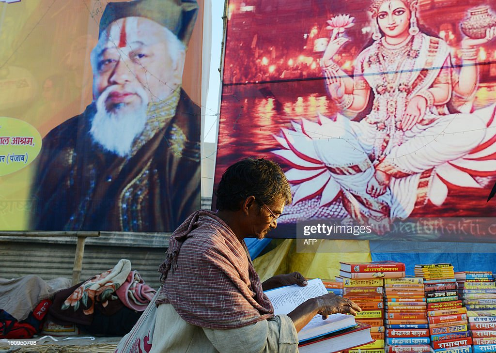 A Hindu devotee browses through books on Hinduism as he sits in front of bill boards depicting the Hindu god Laxshmi (R) and an unidentified guru at Sangam or the confluence of the Yamuna, Ganges and mythical Saraswati rivers during the Kumbh Mela festival in Allahabad February 8, 2013. The Kumbh Mela will see up to 100 million worshippers gather over 55 days to take a ritual bath in the holy waters, believed to cleanse sins and bestow blessings.