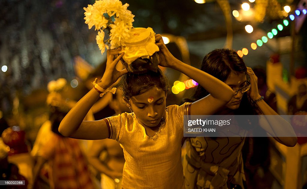 A Hindu devotee carries a milk pot on her head for offering during the Thaipusam Festival at the Batu Caves on the outskirts of Kuala Lumpur on January 28, 2013. The Hindu festival of Thaipusam, which commemorates the day when Goddess Pavarthi gave her son Lord Muruga an invincible lance with which he destroyed evil demons, is celebrated by some two million ethnic Indians in Malaysia and Singapore. AFP PHOTO / Saeed KHAN