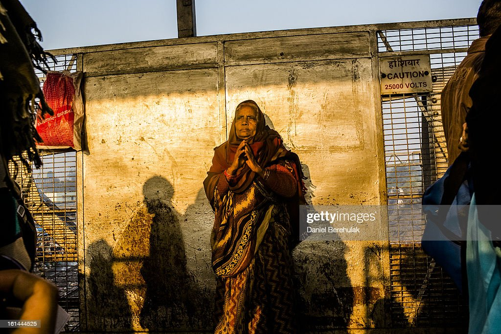 A Hindu devotee clasps her hands together as she waits for her train as people move through Allahabad train station, the site of last night's stampede, as people arrive and depart from the Maha Kumbh Mela on February 11, 2013 in Allahabad, India. According to a government sources report, at least 36 people died in a stampede on a stair case as a train was pulling up on the busiest day of the Maha Kumbh Mela. The Maha Kumbh Mela, believed to be the largest religious gathering on earth, is held every 12 years on the banks of Sangam, the confluence of the holy rivers Ganga, Yamuna and the mythical Saraswati. The Kumbh Mela alternates between the cities of Nasik, Allahabad, Ujjain and Haridwar every three years. The Maha Kumbh Mela celebrated at the holy site of Sangam in Allahabad, is the largest and holiest, celebrated over 55 days, and is expected to attract over 100 million people.