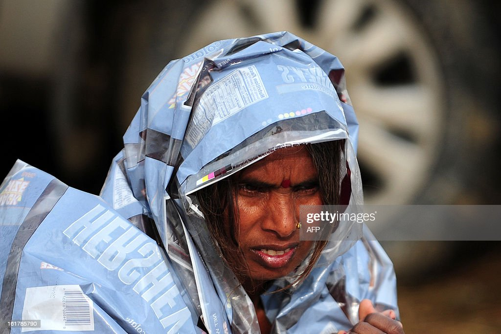 A Hindu devotee covers herself with a plastic sheet during rain in Allahabad on February 16, 2013. Moderate to heavy rains fell across northern India February 16, with night temperatures expected to drop in several areas across the region.