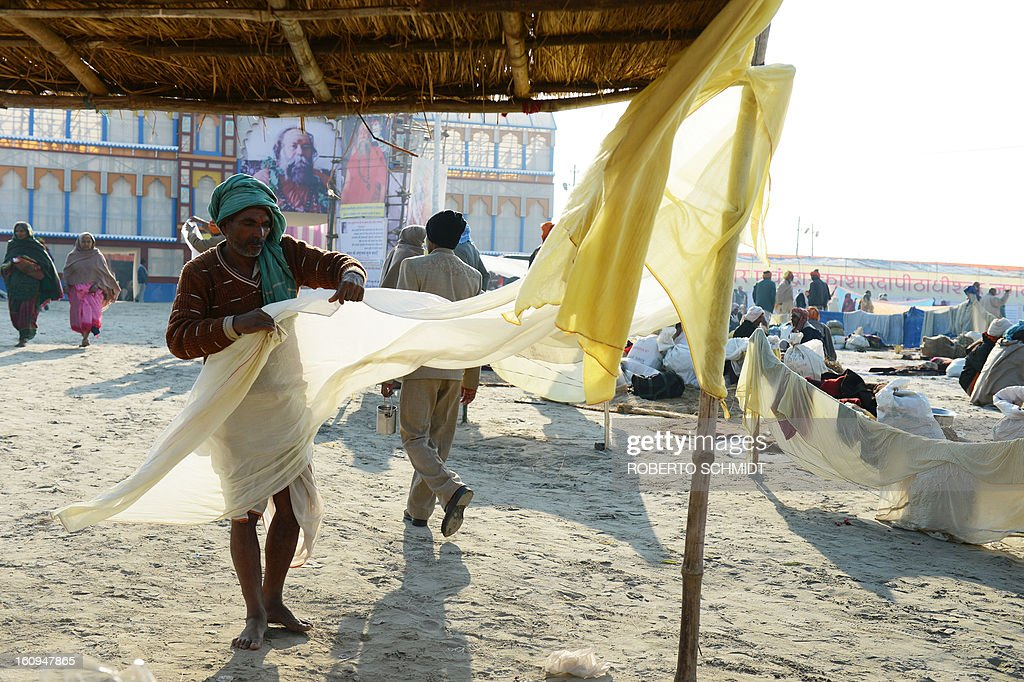 A Hindu devotee folds his dhoti after drying it in the wind moments after he bathed in the waters where the Yamuna and the Ganges river come together during the Maha Kumbh Mela festival in Allahabad on February 8, 2013. The Kumbh Mela in the town of Allahabad will see up to 100 million worshippers gather over 55 days to take a ritual bath in the holy waters, believed to cleanse sins and bestow blessings.