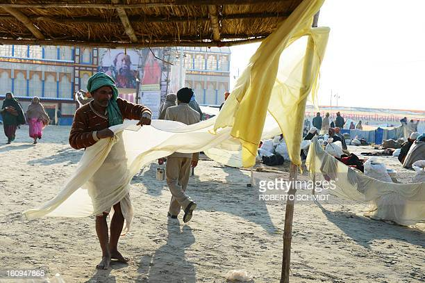 A Hindu devotee folds his dhoti after drying it in the wind moments after he bathed in the waters where the Yamuna and the Ganges river come together...