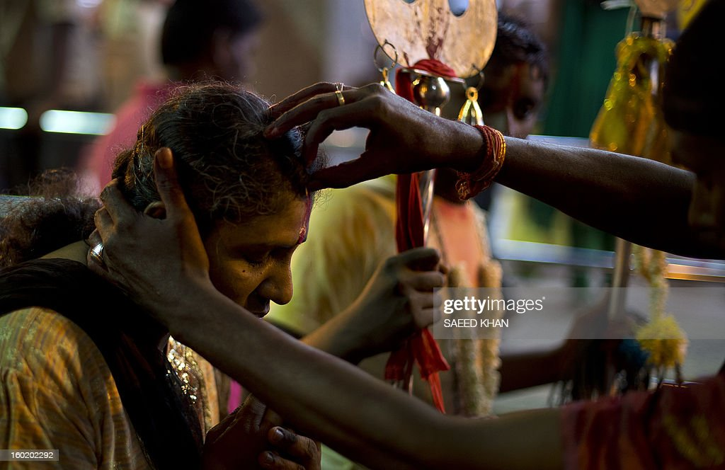 A Hindu devotee gets blessing during the Thaipusam Festival on the outskirts of Kuala Lumpur on January 28, 2013. The Hindu festival of Thaipusam, which commemorates the day when Goddess Pavarthi gave her son Lord Muruga an invincible lance with which he destroyed evil demons, is celebrated by some two million ethnic Indians in Malaysia and Singapore. AFP PHOTO / Saeed KHAN