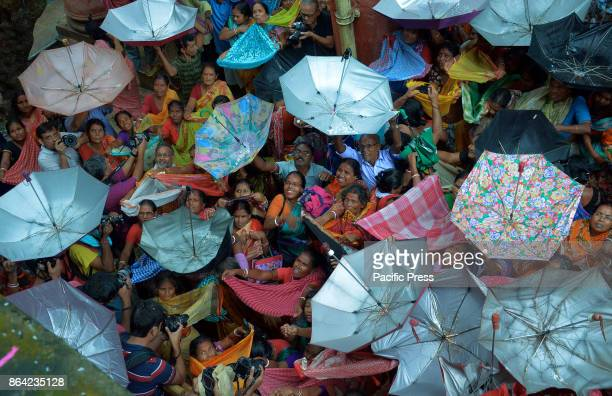 Hindu devotee hold up umbrella to receive holly rice as offering being distributed by a temple authority on the occasion of the Annakut festival