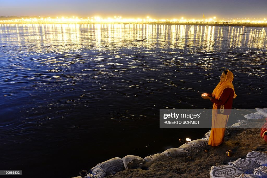 A Hindu devotee holds a candle in her hands as she prays on the shore of the confluence of the Yomuna and the Ganges river at the Sangam during the Maha Kumbh festival in Allahabad on February 7, 2013. The Kumbh Mela in the town of Allahabad will see up to 100 million worshippers gather over 55 days to take a ritual bath in the holy waters, believed to cleanse sins and bestow blessings. AFP PHOTO/ROBERTO SCHMIDT
