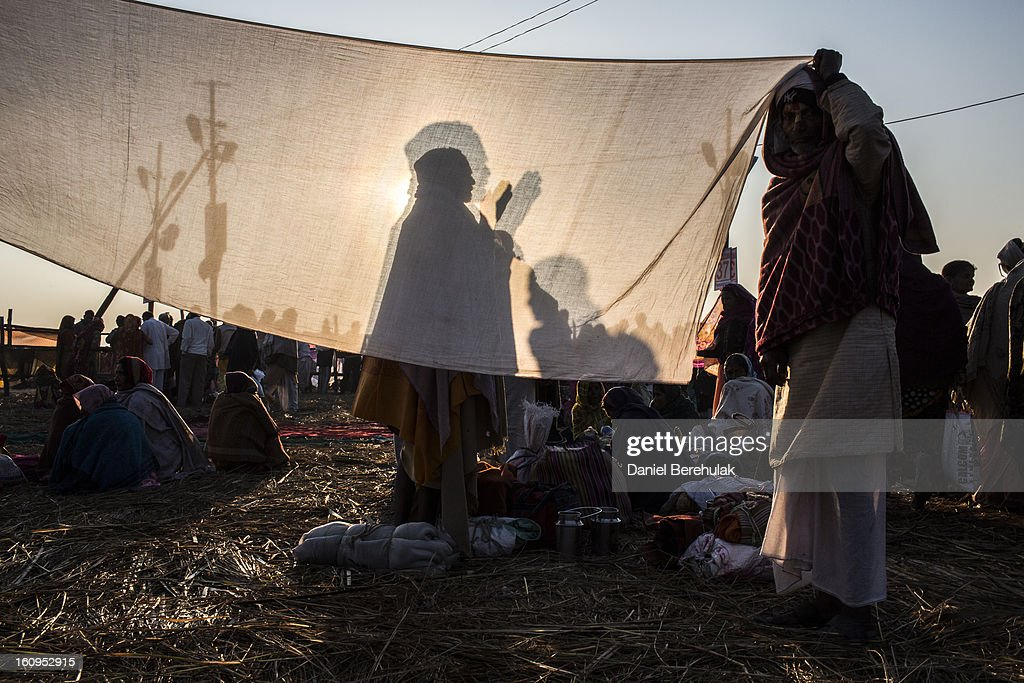 A Hindu devotee is seen silhouetted through a drying sari as he prays after having bathed on the banks of Sangam, the confluence of the holy rivers Ganges, Yamuna and the mythical Saraswati, during the Maha Kumbh Mela on February 8, 2013 in Allahabad, India. The Maha Kumbh Mela, believed to be the largest religious gathering on earth is held every 12 years on the banks of Sangam, the confluence of the holy rivers Ganga, Yamuna and the mythical Saraswati. The Kumbh Mela alternates between the cities of Nasik, Allahabad, Ujjain and Haridwar every three years. The Maha Kumbh Mela celebrated at Sangam, is the largest and holiest, celebrated over 55 days, it is expected to attract over 100 million pilgrims who will bathe in holy waters to wash away their sins.