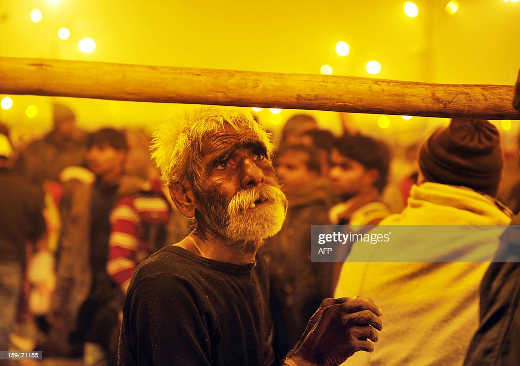 A Hindu devotee looks up as he joins a crowd of thousands after he dipped in the waters of the Sangham or the confluence of the the Yamuna and Ganges rivers during the Kumbh Mela in Allahabad on January 14, 2013. Hundreds of thousands of Hindu pilgrims led by naked, ash-covered holy men streamed into the sacred river Ganges at the start of the world's biggest religious festival. The Kumbh Mela in the Indian town of Allahabad will see up to 100 million worshippers gather over the next 55 days to take a ritual bath in the holy waters, believed to cleanse sins and bestow blessings. AFP PHOTO/ Sanjay Kanojia