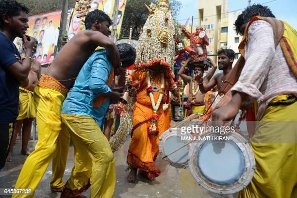 A Hindu devotee of Goddess Angala Parameshwari carries = the sacred flower 'Karaga' on their head as they dance during the culmination of the 'Mayana...
