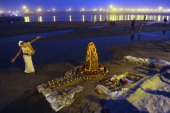 A Hindu devotee performs an evening ritual at Sangam the confluence of the rivers Ganges and Yamuna and mythical Saraswati during the Maha Kumbh Mela...