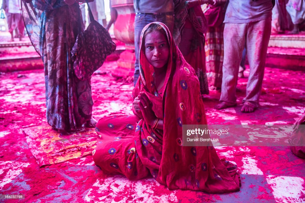 A Hindu devotee prays after having played with color at the Ladli Ji temple during Lathmaar Holi celebrations on March 21, 2013 in the village of Barsana, near Mathura, India. The tradition of playing with colours on Holi draws its roots from a legend of Radha and the Hindu God Krishna. It is believed that young Krishna was jealous of Radha's fair complexion since he himself was himself very dark. After questioning his mother Yashoda on the darkness of his complexion, Yashoda, teasingly asked him to colour Radha's face in which ever colour he wanted. In a mischievous mood, Krishna applied colour on Radha's face. The tradition of applying color on one's beloved is being religiously followed till date.