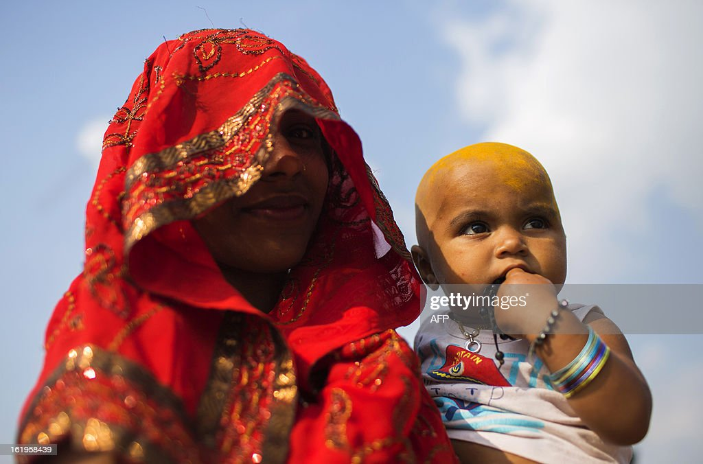 A Hindu devotee prepares to bathe her daughter in the Sangam, the confluence of the Yamuna, Ganges and mythical Saraswati rivers during the Kumbh Mela in Allahabad on February 18, 2013. The Kumbh Mela in the town of Allahabad will see up to 100 million worshippers gather over 55 days to take a ritual bath in the holy waters, believed to cleanse sins and bestow blessings. AFP PHOTO/ Andrew Caballero-Reynolds