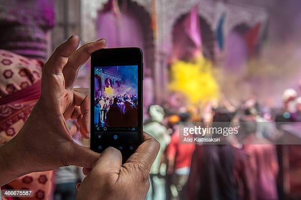 Hindu devotee records the Holi celebrations by his smartphone during the Holi festival in the Banke Bihari temple Known as the festival of colours...