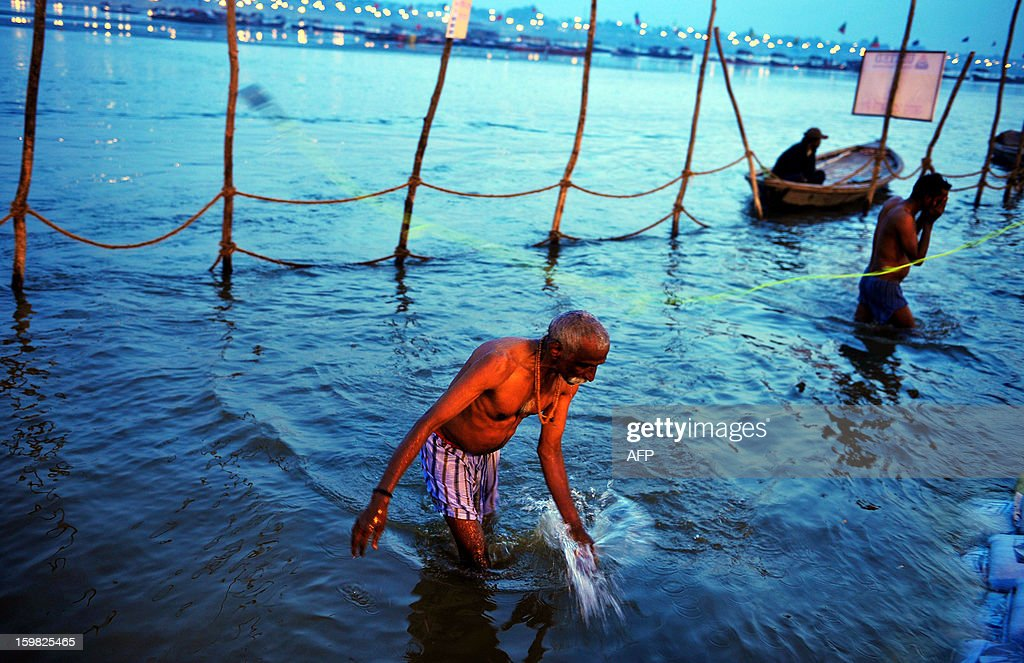 A Hindu devotee returns after taking a dip in the Sangam, the confluence of the rivers Ganges and Yamuna in Allahabad on January 21, 2013. The Kumbh Mela in the Indian town of Allahabad will see up to 100 million worshippers gather over the next 55 days to take a ritual bath in the holy waters, believed to cleanse sins and bestow blessings. AFP PHOTO/ Sanjay KANOJIA