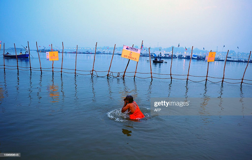 A Hindu devotee takes a dip at Sangam, the confluence of the Rivers Ganges, Yamuna and mythical Saraswati, during the Maha Kumbh Mela in Allahabad on January 18, 2013. The Kumbh Mela in the Indian town of Allahabad will see up to 100 million worshippers gather over the next 55 days to take a ritual bath in the holy waters, believed to cleanse sins and bestow blessings. AFP PHOTO/ Sanjay KANOJIA