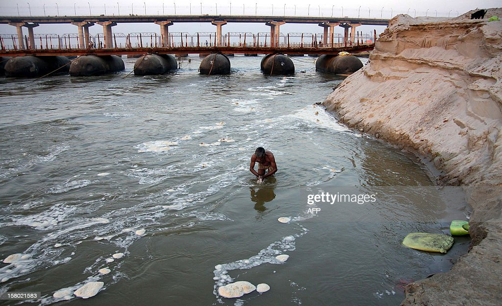 A Hindu devotee takes a holy dip in the polluted river Ganga (Ganges) in Allahabad on December 9, 2012. The Ganga is the largest river in India with an extraordinary religious importance for Hindus - flowing through 29 cities, a large proportion of the pollution of the river is from the population of these cities through domestic use. AFP PHOTO/ Sanjay KANOJIA