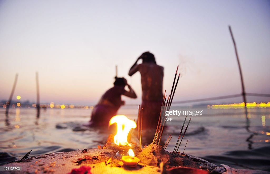 Hindu devotees bathe at Sangam, the confluence of the Yamuna, Ganges and mythical Saraswati rivers after sundown at the Kumbh Mela in Allahabad on February 9, 2013. The Kumbh Mela in the town of Allahabad will see up to 100 million worshippers gather over 55 days to take a ritual bath in the holy waters, believed to cleanse sins and bestow blessings.