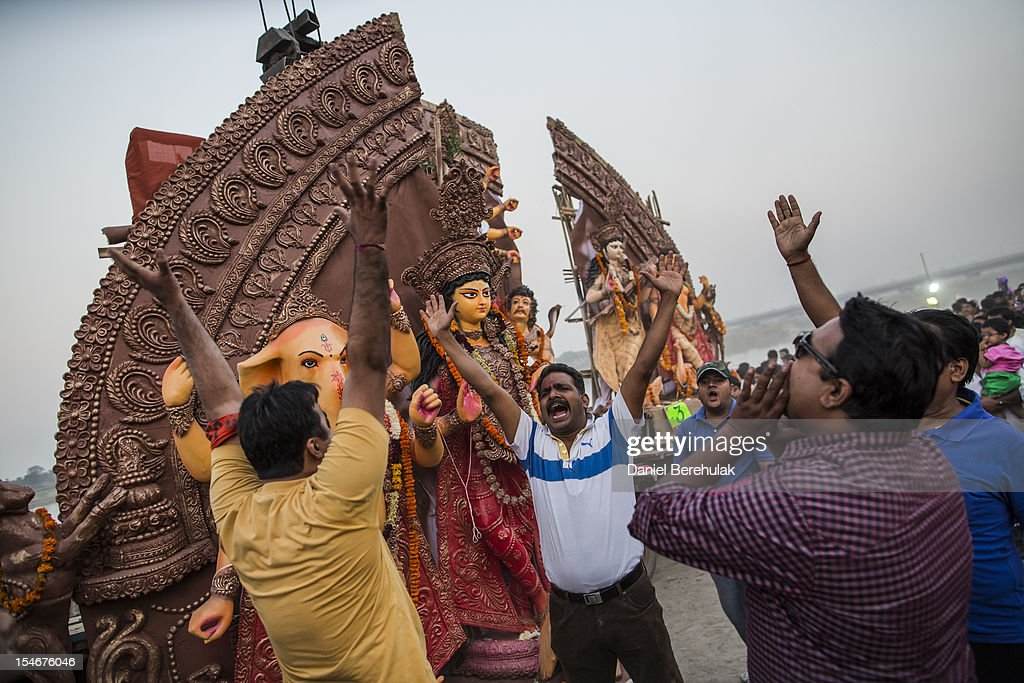 Hindu devotees celebrate prior to immersing an idol of Goddess Durga into the Yamuna river on the last day of the Durga Puja festival on October 24, 2012 in Delhi, India. The festival celebrates the worship of the Hindu Goddess Durga, who in Hindu Mythology is celebrated as the Goddess of power and the victor of good over evil.