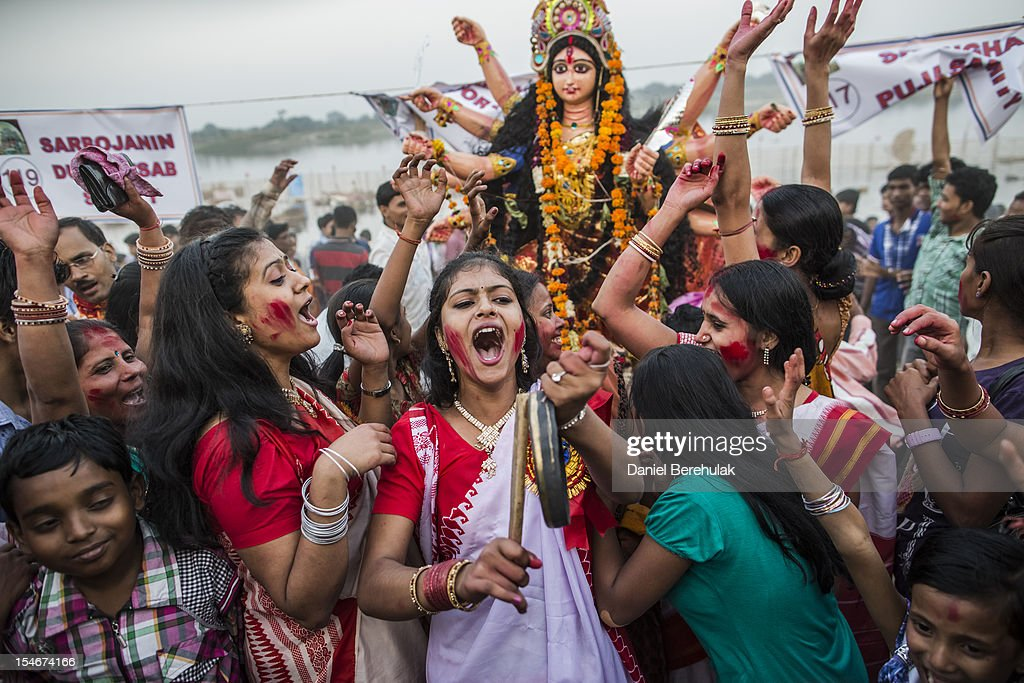 Hindu devotees chant prior to immersing an idol of Goddess Durga into the Yamuna river on the last day of the Durga Puja festival on October 24, 2012 in Delhi, India. The festival celebrates the worship of the Hindu Goddess Durga, who in Hindu Mythology is celebrated as the Goddess of power and the victor of good over evil.