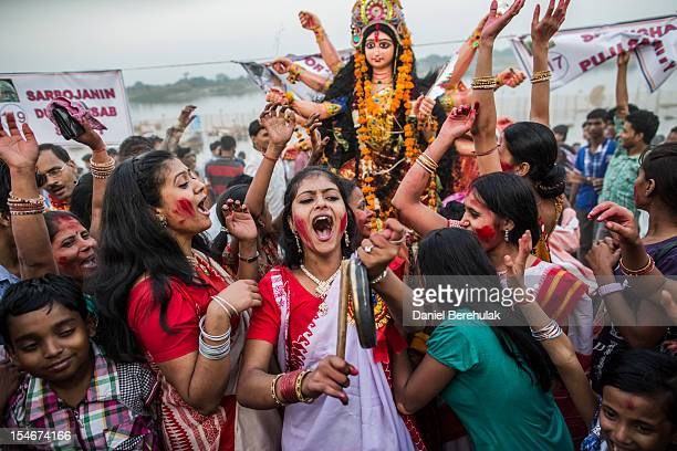 Hindu devotees chant prior to immersing an idol of Goddess Durga into the Yamuna river on the last day of the Durga Puja festival on October 24 2012...