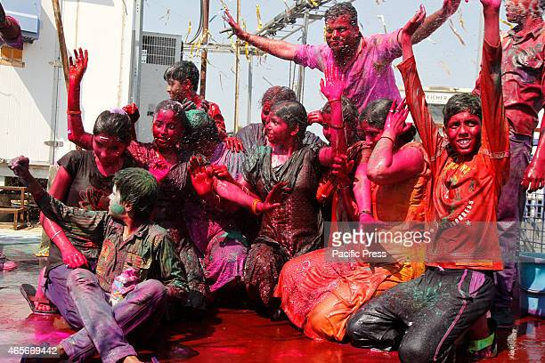 Hindu devotees cover their body with colors and dances as the water sprinkled on them as they celebrate Holi festival The Holi festival involves...