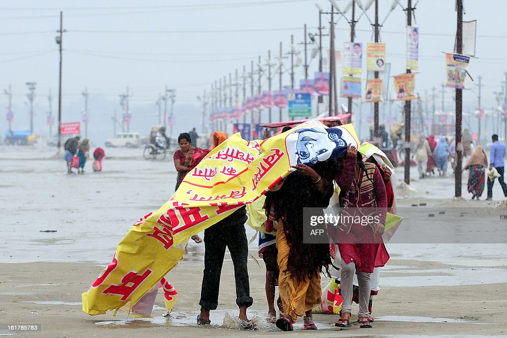 Hindu devotees cover themselves with a plastic hoarding during rain in Allahabad on February 16, 2013. Moderate to heavy rains fell across northern India February 16, with night temperatures expected to drop in several areas across the region.