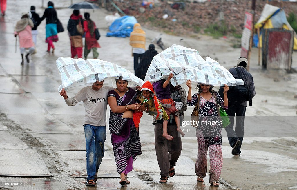 Hindu devotees cover themselves with plastic sheets as they walk in heavy rain at Sangam, the confluence of the Yamuna, Ganges and mythical Saraswati rivers and the site of the Kumbh Mela in Allahabad on February 23, 2013. The Kumbh Mela in the town of Allahabad will see up to 100 million worshippers gather over 55 days to take a ritual bath in the holy waters, believed to cleanse sins and bestow blessings.