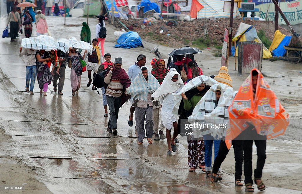 Hindu devotees cover themselves with plastic sheets during a heavy rainfall at Sangam, the confluence of the Yamuna, Ganges and mythical Saraswati rivers and the site of the Kumbh Mela in Allahabad on February 23, 2013. The Kumbh Mela in the town of Allahabad will see up to 100 million worshippers gather over 55 days to take a ritual bath in the holy waters, believed to cleanse sins and bestow blessings.