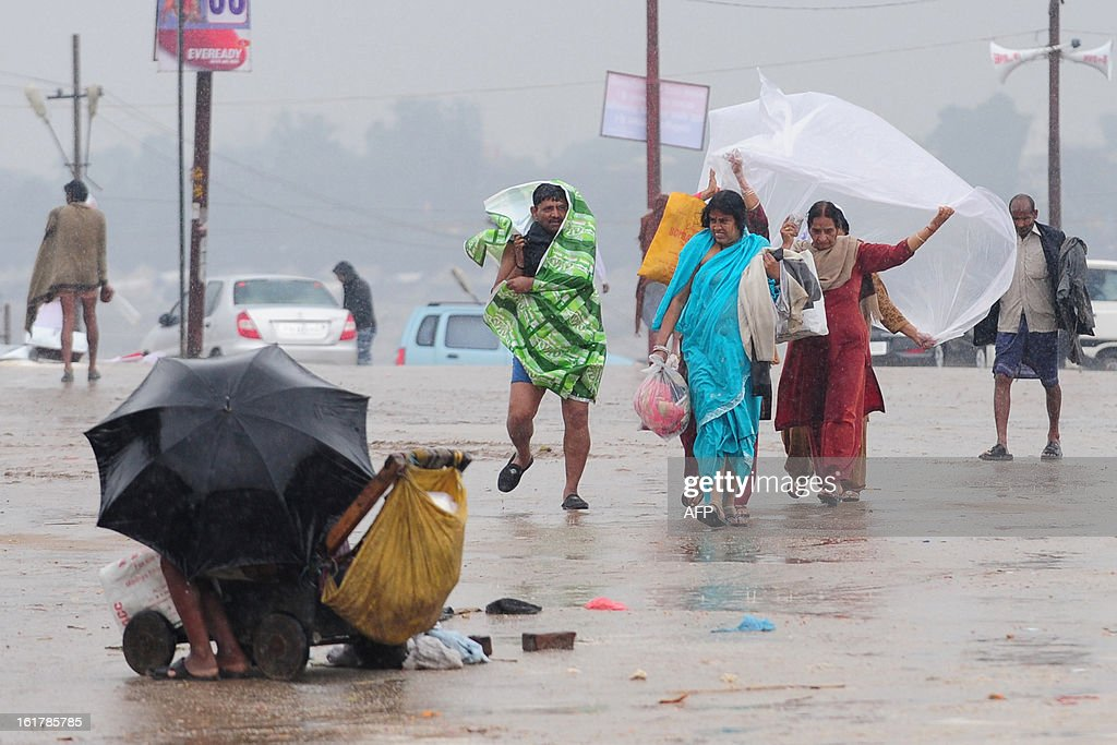Hindu devotees cover themselves with plastic sheets during heavy rain at Sangam in Allahabad on February 16, 2013. Moderate to heavy rains fell across northern India February 16, with night temperatures expected to drop in several areas across the region.