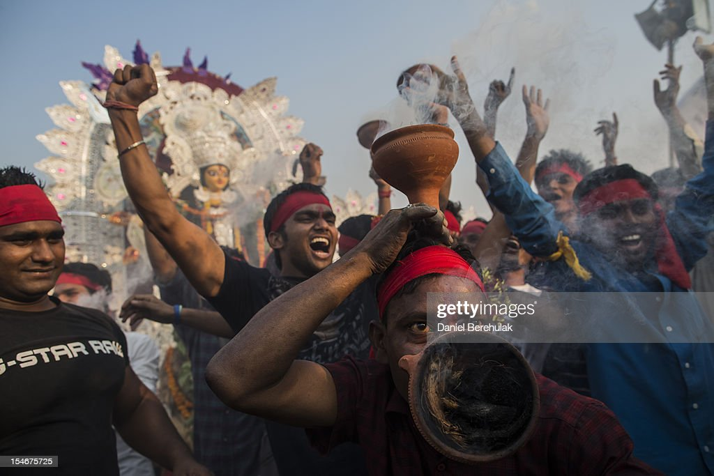 Hindu devotees dance and celebrate as they walk down to immerse an idol of Goddess Durga into the Yamuna river on the last day of the Durga Puja festival on October 24, 2012 in Delhi, India. The festival celebrates the worship of the Hindu Goddess Durga, who in Hindu Mythology is celebrated as the Goddess of power and the victor of good over evil.