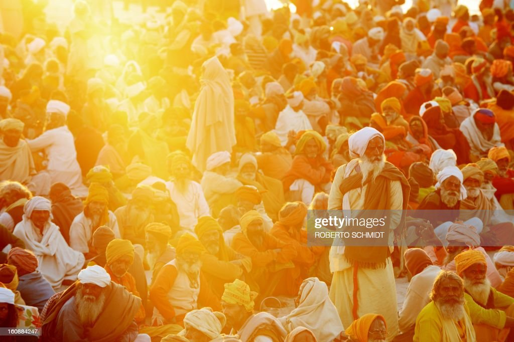 Hindu devotees gather in the shore of the confluence of the Yomuna and the Ganges river at the Sangam in the late afternoon as they wait to be served a free meal organized by an ashram during the Maha Kumbh festival in Allahabad on February 7, 2013. The Kumbh Mela in the town of Allahabad will see up to 100 million worshippers gather over 55 days to take a ritual bath in the holy waters, believed to cleanse sins and bestow blessings.