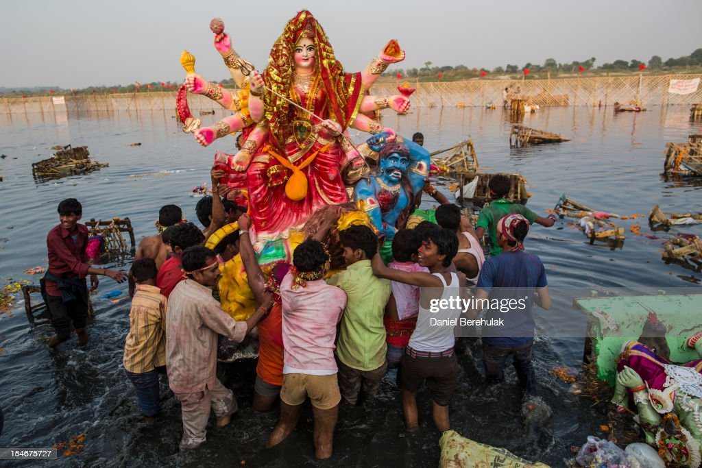 Hindu devotees immerse an idol of Goddess Durga into the Yamuna river on the last day of the Durga Puja festival on October 24, 2012 in Delhi, India. The festival celebrates the worship of the Hindu Goddess Durga, who in Hindu Mythology is celebrated as the Goddess of power and the victor of good over evil.
