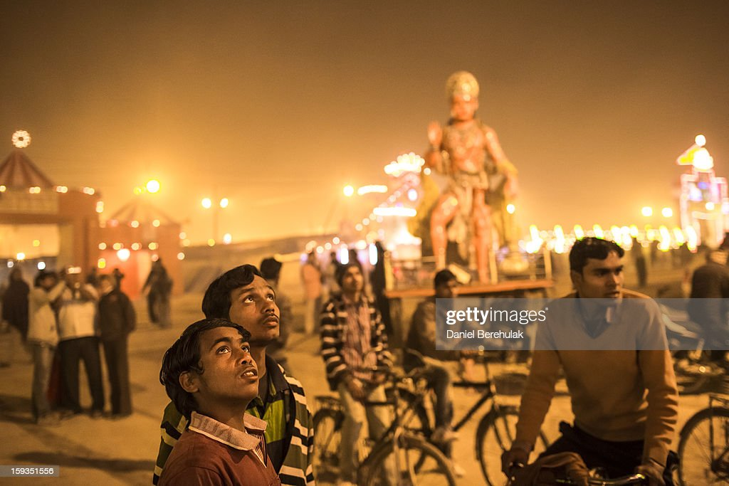 Hindu devotees look up at the gate of the Shri Panchayati Akhara Bara Udasin as they gather ahead of the Maha Kumbh Mela on January 12, 2013 in Allahabad, India. The Maha Kumbh Mela, believed to be the largest religious gathering on earth, is held every 12 years on the banks of Sangam, the confluence of the holy rivers Ganga, Yamuna and the mythical Saraswati. The gathering is celebrated at the holy site of Sangam in Allahabad over 55 days and attracts over 100 million people.
