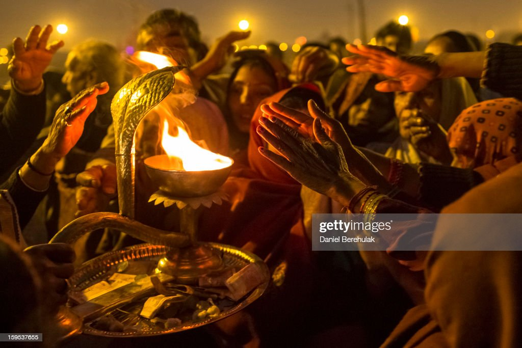 Hindu devotees move their hands towards the flames presented by a priest during an aarti ceremony on the banks of the Ganges river during the Maha Kumbh Mela on January 15, 2013 in Allahabad, India. The Maha Kumbh Mela, believed to be the largest religious gathering on earth is held every 12 years on the banks of Sangam, the confluence of the holy rivers Ganga, Yamuna and the mythical Saraswati. The Kumbh Mela alternates between the cities of Nasik, Allahabad, Ujjain and Haridwar every three years. The Maha Kumbh Mela celebrated at the holy site of Sangam in Allahabad, is the largest and holiest, celebrated over 55 days, it is expected to attract over 100 million people.