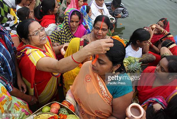 Hindu devotees offer prayers to Suraya Dev on sunset standing in the waters of the River Yamuna to mark Chhath Puja festival During Chhath an ancient...