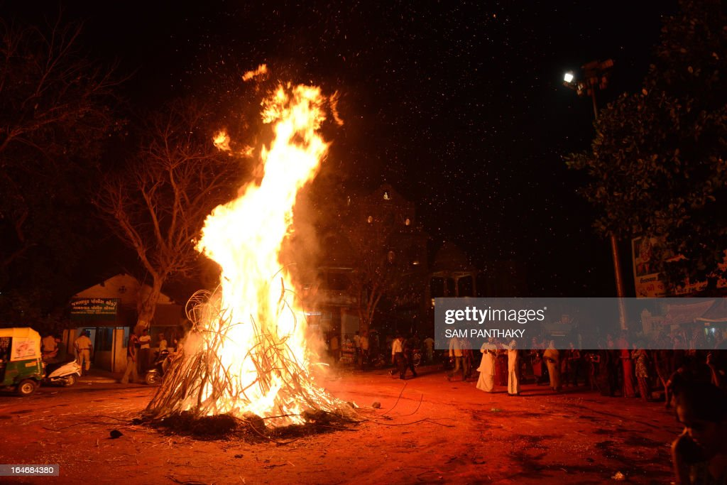 Hindu devotees participate in the Holika bonfire, outside the Lord Jagannath Mandir in Ahmedabad on March 26, 2013. The priests from Lord Jagannath Mandir and the police officers together ignited Holika which symbolizes the destruction of evil, to mark Holi. AFP PHOTO / Sam PANTHAKY