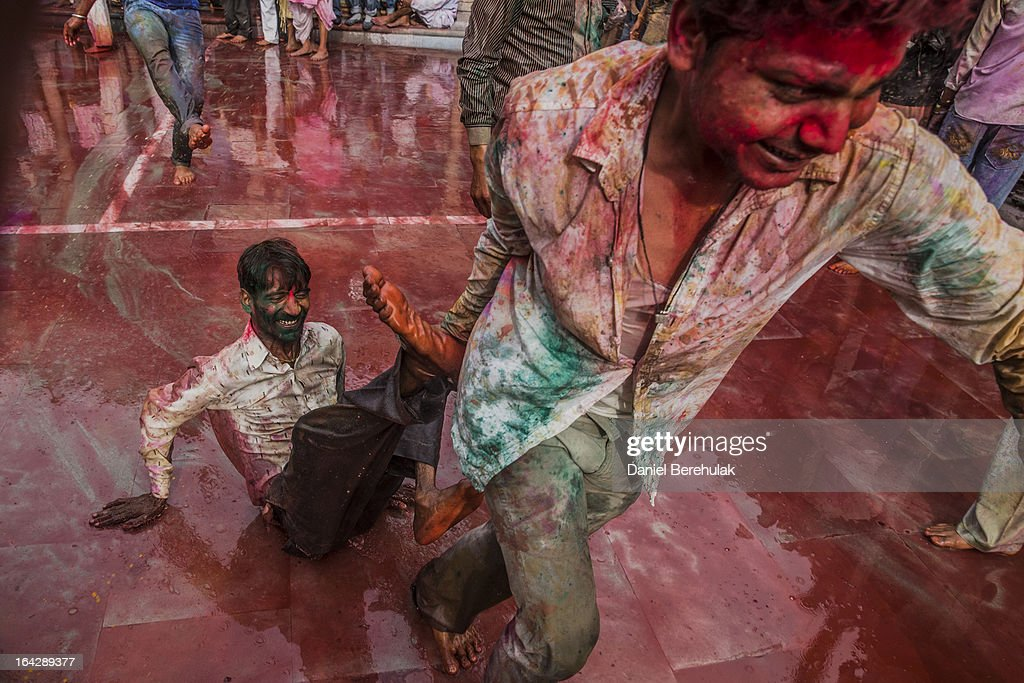 Hindu devotees play with color during Lathmaar Holi celebrations on March 22, 2013 in the village of Nundgaon near Mathura, India. The tradition of playing with colours on Holi draws its roots from a legend of Radha and the Hindu God Krishna. It is believed that young Krishna was jealous of Radha's fair complexion since he himself was himself very dark. After questioning his mother Yashoda on the darkness of his complexion, Yashoda, teasingly asked him to color Radha's face in which ever color he wanted. In a mischievous mood, Krishna applied color on Radha's face. The tradition of applying color on one's beloved is being religiously followed until today.