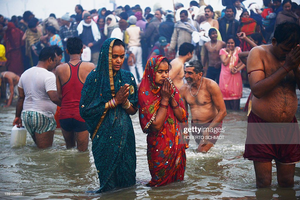 Hindu devotees pray as they bathe in the Sangham or the confluence of the the Yamuna and Ganges rivers during the Kumbh Mela in Allahabad on January 14, 2013. Hundreds of thousands of Hindu pilgrims led by naked, ash-covered holy men streamed into the sacred river Ganges at the start of the world's biggest religious festival. The Kumbh Mela in the Indian town of Allahabad will see up to 100 million worshippers gather over the next 55 days to take a ritual bath in the holy waters, believed to cleanse sins and bestow blessings.