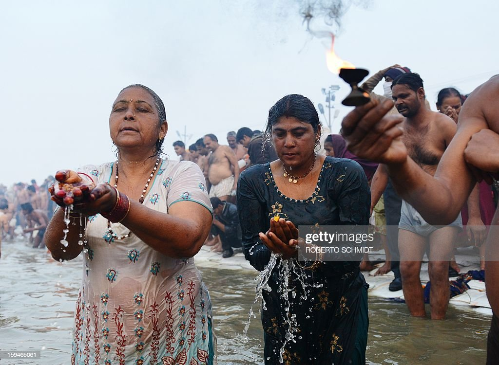 Hindu devotees pray in the waters of the Sangham or the confluence of the the Yamuna and Ganges rivers during the Kumbh Mela in Allahabad on January 14, 2013. Hundreds of thousands of Hindu pilgrims led by naked, ash-covered holy men streamed into the sacred river Ganges on Monday at the start of the world's biggest religious festival. The Kumbh Mela in the Indian town of Allahabad will see up to 100 million worshippers gather over the next 55 days to take a ritual bath in the holy waters, believed to cleanse sins and bestow blessings. Before daybreak on Monday, a day chosen by astrologers as auspicious, hundreds of gurus, some brandishing swords and tridents, ran into the swirling and freezing waters for the first bath, signalling the start of events.