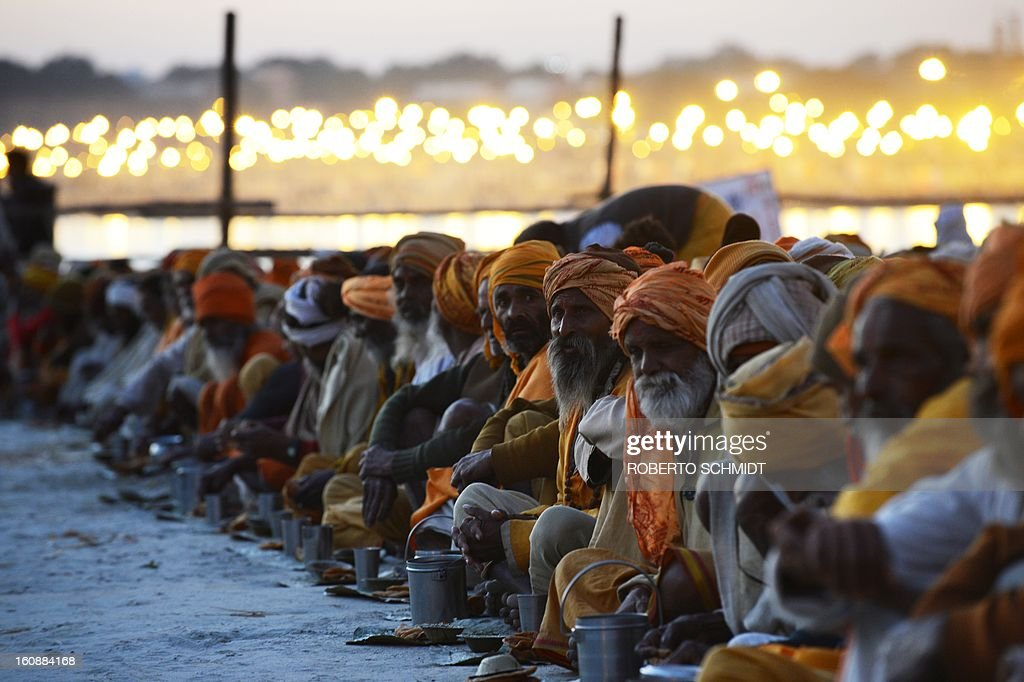 Hindu devotees sit near the shore of the confluence of the Yomuna and the Ganges river at the Sangam in the early evening as they wait to be served a free meal organized by an ashram during the Maha Kumbh festival in Allahabad on February 7, 2013. The Kumbh Mela in the town of Allahabad will see up to 100 million worshippers gather over 55 days to take a ritual bath in the holy waters, believed to cleanse sins and bestow blessings.