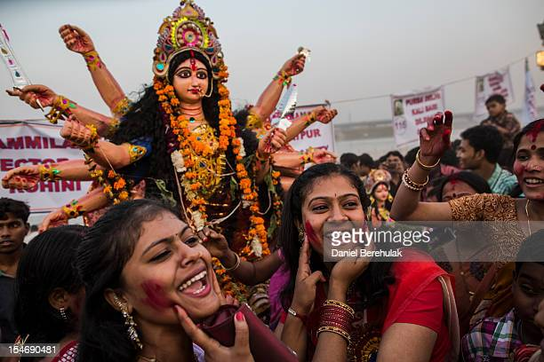 Hindu devotees smear red dye on each others faces as they transport an idol of Goddess Durga to be immersed into the Yamuna river on the last day of...