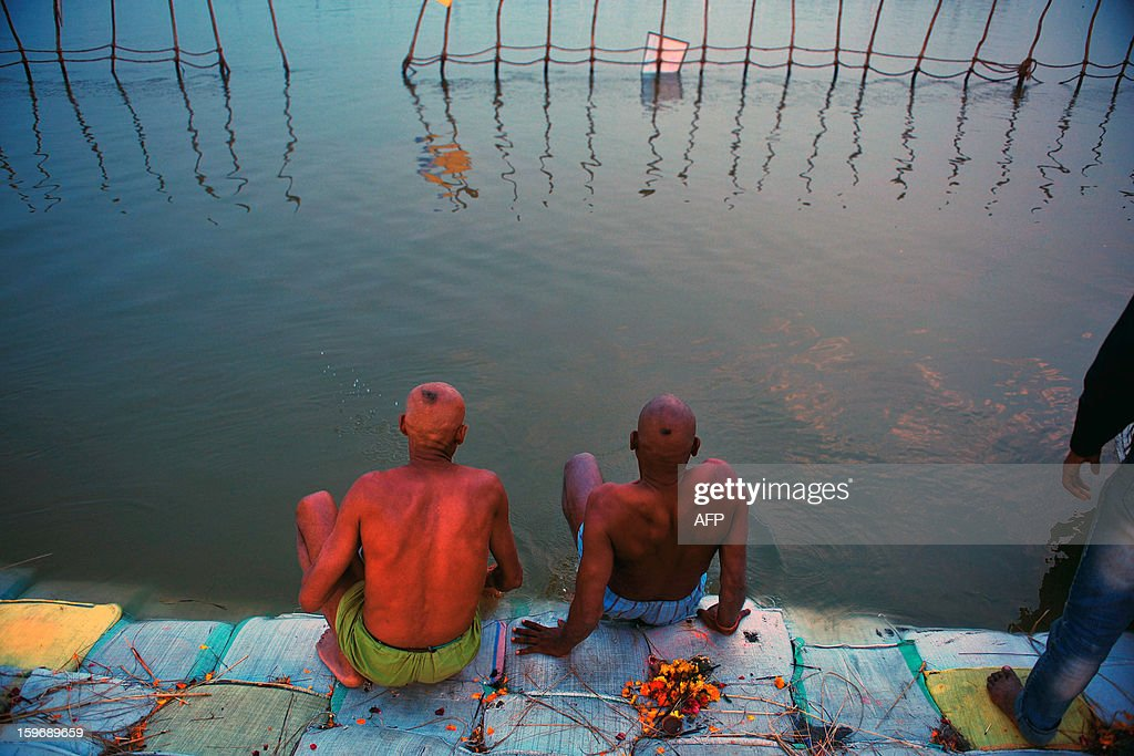 Hindu devotees take a dip at Sangam, the confluence of the Rivers Ganges, Yamuna and mythical Saraswati, during the Maha Kumbh Mela in Allahabad on January 18, 2013. The Kumbh Mela in the Indian town of Allahabad will see up to 100 million worshippers gather over the next 55 days to take a ritual bath in the holy waters, believed to cleanse sins and bestow blessings. AFP PHOTO/ Sanjay KANOJIA